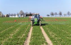 Traktor auf spritzender Plage des Feldes Stockbild