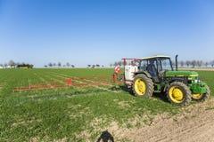 Traktor auf spritzender Plage des Feldes Lizenzfreies Stockfoto