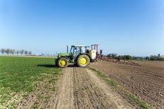 Traktor auf spritzender Plage des Feldes Stockfoto