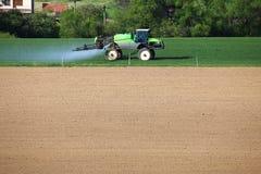 Traktor befruchtet grünes Weizenfeld Stockbilder
