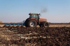Traktor bei der Arbeit über Bauernhof stockbild