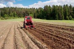 Traktor bei der Arbeit über ein Feld Stockfotografie