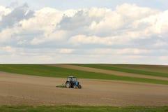 Traktor bei der Arbeit, die im Frühjahr ein Feld, Ackerland, gepflogen kultiviert Lizenzfreie Stockbilder