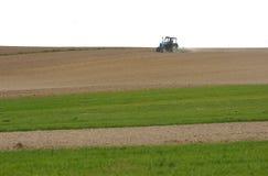 Traktor bei der Arbeit, die im Frühjahr ein Feld, Ackerland, gepflogen kultiviert Stockfotos