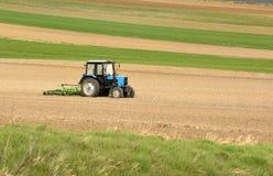Traktor bei der Arbeit, die im Frühjahr ein Feld, Ackerland, gepflogen kultiviert Stockbild