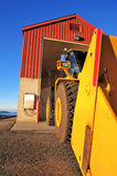 Traktor And Building. Large front loading tractor and salt storage building against a clear blue sky Stock Photography