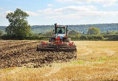 Traktor, der über einem Feld von Weizen Stubble pflügt stockbild