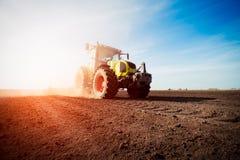 Traktor, der an Ackerland auf Sonnenuntergang arbeitet Stockbilder