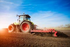Traktor, der an Ackerland auf Sonnenuntergang arbeitet Stockfotografie