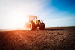 Traktor, der an Ackerland auf Sonnenuntergang arbeitet Lizenzfreie Stockfotografie