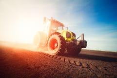 Traktor, der an Ackerland auf Sonnenuntergang arbeitet Lizenzfreie Stockfotos
