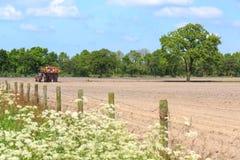 Traktor, der an acultivated Feld in einer Landschaftslandschaft arbeitet Lizenzfreie Stockfotos