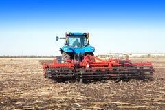 Traktor, der auf einem Gebiet arbeitet Lizenzfreie Stockfotos