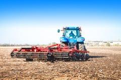 Traktor, der auf einem Gebiet arbeitet Lizenzfreie Stockfotografie