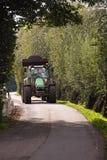 Traktor, der auf Landstraße antreibt Lizenzfreies Stockbild
