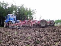 Traktor, der das Feld bevor dem Frühlingspflanzen pflügt Nahaufnahme, Landschaft stockfoto
