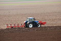 Traktor, der das Feld pflügt Stockbilder