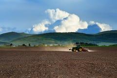 Traktor, der an dem Feld arbeitet Lizenzfreies Stockfoto