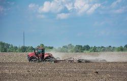 Traktor, der an dem Feld, ein moderner landwirtschaftlicher Transport, Bearbeitung des Landes arbeitet Lizenzfreie Stockfotografie