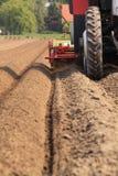 Traktor, der die Geraden des Landes bearbeitet Lizenzfreie Stockfotos