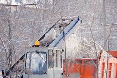 Traktor, der die Straße vom Schnee säubert Bagger säubert die Straßen von großen Mengen Schnee in der Stadt Arbeitskraftschleifen Stockfotografie
