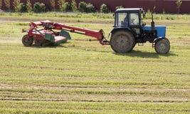 Traktor, der die Wiese mäht stockfotografie