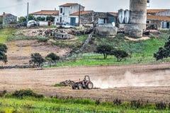 Traktor, der ein braunes Feld pflügt Lizenzfreies Stockfoto