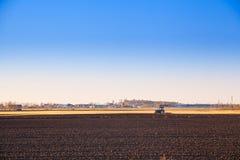 Traktor, der ein Feld für das Frühlingspflanzen pflügt Stockbilder