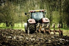 Traktor, der ein Feld im Frühjahr pflügt Lizenzfreies Stockbild