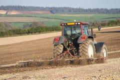 Traktor, der ein Feld pflügt. Stockbilder