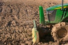 Traktor, der ein Feld pflügt Stockbilder