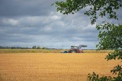 Traktor, der ein gelbes Kornfeld kreuzt Lizenzfreie Stockfotos