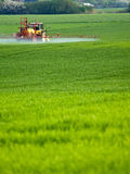 Traktor, der ein grünes Feld sprüht Lizenzfreies Stockbild