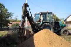 Traktor, der ein Loch mit Schaufel gräbt Stockbild