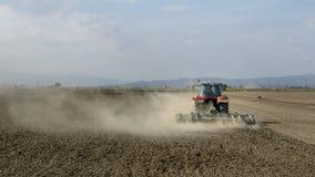 Traktor, der ein staubiges Feld mit unerkennbaren Leuten pflügt stockbild