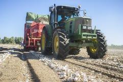 Traktor, der eine Zwiebelerntemaschine zieht Lizenzfreie Stockfotos