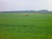 Traktor, der an einem grünen Feld mit Ernten arbeitet Lizenzfreie Stockfotografie