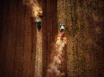 Traktor, der Feld, Felsen und Staub in frühem MO oben tretend kultiviert stockfoto
