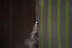 Traktor, der Feld am Frühling, Vogelperspektive kultiviert Lizenzfreie Stockfotografie