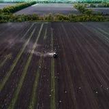Traktor, der Feld am Frühling, Vogelperspektive kultiviert Stockbilder
