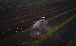 Traktor, der Feld am Frühling, Vogelperspektive kultiviert Stockbild