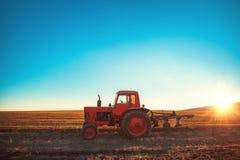 Traktor, der Feld am Frühling während des Sonnenuntergangs kultiviert lizenzfreie stockbilder