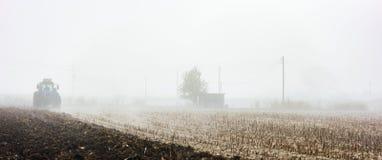 Traktor, der Feld pflügt Stockbilder