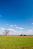 Traktor, der an Feldern arbeitet Lizenzfreies Stockbild