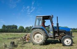 Traktor, der grünes Feld mäht stockfotos