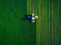 Traktor, der grünes Feld mäht Stockbilder