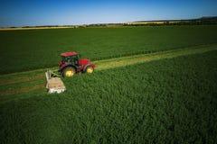 Traktor, der grünes Feld mäht Lizenzfreie Stockfotos