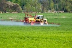 Traktor, der grünes Feld sprüht stockbild