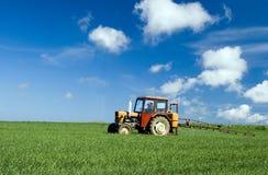 Traktor, der grünes Feld sprüht Lizenzfreies Stockfoto