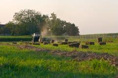 Traktor, der Heuballen herstellt Stockfotos